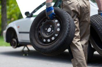 Back view of a mechanic holding a two car wheel